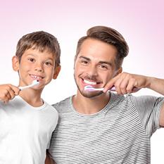 Mały chłopiec i jego ojciec szczotkuje zęby